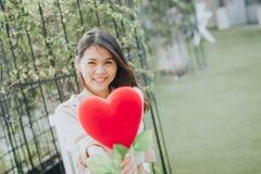 Azjatycka kobieta w miłości teraźniejszości kształta kierowym kwiacie zdjęcie stock