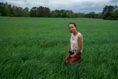 Azjatycka kobieta w polu otaczaj?cym traw? obrazy stock