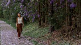 Azjatycka kobieta w sarongu odprowadzeniu na chodniczku zakrywającym z żałość płatkami obrazy royalty free