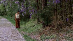 Azjatycka kobieta w sarongu odprowadzeniu na chodniczku zakrywaj?cym z ?a?o?? p?atkami fotografia royalty free