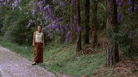 Azjatycka kobieta w sarongu odprowadzeniu na chodniczku zakrywaj?cym z ?a?o?? p?atkami obrazy stock