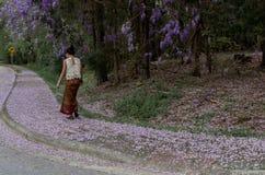Azjatycka kobieta w sarongu odprowadzeniu na chodniczku zakrywaj?cym z ?a?o?? p?atkami zdjęcia royalty free