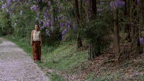 Azjatycka kobieta w sarongu odprowadzeniu na chodniczku zakrywaj?cym z ?a?o?? p?atkami obraz stock