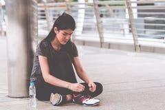 Azjatycka kobieta wiąże shoelace ćwiczenie w nowożytnym mieście obrazy royalty free