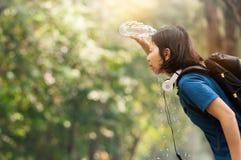 Azjatycka kobieta wycieczkowicza dolewania woda od butelki na jej twarzy z nat Zdjęcia Royalty Free