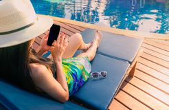 Azjatycka kobieta z kapeluszem i swimsuit siedzimy dalej sunbed przy poolside i używać basenem smartphone na wakacje dziewczyna zdjęcie royalty free