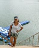 Azjatycka kobieta z kapeluszową pozycją na odgórnych krokach fotografia stock