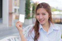 Azjatycka kobieta z uśmiechniętą twarzy i białej pustą kartą w jej ręce Obraz Royalty Free