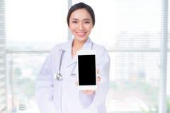 Azjatycka kobiety lekarka pokazuje smartphone ekran obraz stock