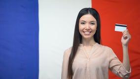 Azjatycka kobiety mienia karta kredytowa przeciw francuz flagi tłu, przelew pieniędzy zbiory