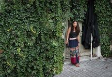 Azjatycka kobiety pozycja przed bluszcz zakrywającą ścianą obrazy royalty free