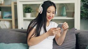 Azjatycka młoda dama z pięknym długim czarni włosy słucha muzyka przez hełmofonów i używa smartphone cieszyć się zdjęcie wideo