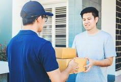 Azjatycka mężczyzna ręka akceptuje dostawę boksuje od fachowego deliveryman w domu zdjęcie royalty free