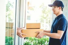 Azjatycka mężczyzna ręka akceptuje dostawę boksuje od fachowego deliveryman w domu zdjęcia royalty free