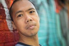 Azjatycka męska pozycja przeciw graffiti ścianie Obrazy Stock