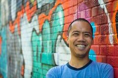 Azjatycka męska pozycja przeciw graffiti ścianie, ono uśmiecha się Zdjęcia Stock