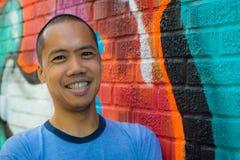 Azjatycka męska pozycja przeciw graffiti ścianie, ono uśmiecha się Zdjęcia Royalty Free