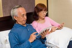 Azjatycka męska używa pastylka w łóżku Obraz Stock