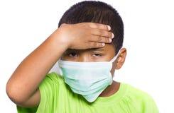 Azjatycka młoda chłopiec jest ubranym rozporządzalną twarzy maskę Obrazy Royalty Free