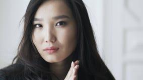 Azjatycka młoda kobieta naciera ona i patrzeje widza ręki zdjęcie wideo