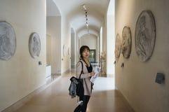 Azjatycka młoda kobieta patrzeje wokoło louvre muzeum i docenia piękno dzieło sztuki zdjęcie stock