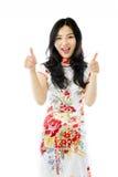 Azjatycka młoda kobieta pokazuje aprobaty od oba ręk odizolowywać na białym tle zdjęcie stock