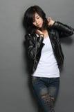 Azjatycka młoda kobieta w czarnej skórzanej kurtce na szarym tle obraz royalty free