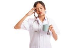Azjatycka młoda kobiety lekarka dostać migrenę z filiżanką kawy Obrazy Royalty Free