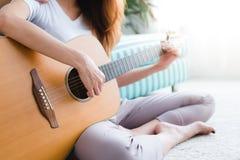 Azjatycka młoda lesbian para bawić się gitarę dla jej kochanka z miłość momentem w sypialni otaczającej z ciepłym światłem słonec Obrazy Stock