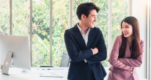 Azjatycka młoda przystojna biznesowego mężczyzny rozmowa z biznesową kobietą w ten sposób śmieszną Dobry zwi?zek w pracowa? Powod zdjęcia stock