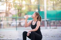 Azjatycka młoda sprawności fizycznej kobiety woda pitna po jogging Zdjęcie Stock