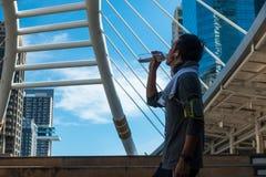 Azjatycka młody człowiek woda pitna po ćwiczenia wśród miasta zdjęcie stock