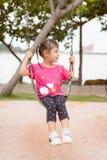 Azjatycka małej dziewczynki sztuka mała dziewczynka i szczęśliwy na huśtawce przy parkiem, zabawę obrazy stock