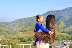 Azjatycka mama cuddle jej córki z miłością na balkonie przy zboczem obrazy royalty free