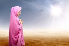 Azjatycka muzułmańska kobieta w przesłony modleniu na pustyni obrazy stock