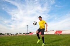Azjatycka nastolatek chłopiec w sportach tworzy w stadionie futbolowym, pra Zdjęcie Stock