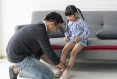 Azjatycka ojciec odzież kuje córki wpólnie w pokoju dziennym w domu obrazy stock