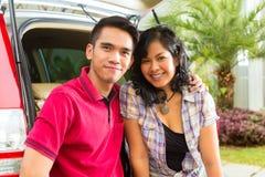 Azjatycka para jest szczęśliwa wewnątrz stać na czele samochód Fotografia Royalty Free