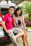 Azjatycka para jest szczęśliwa wewnątrz stać na czele samochód Zdjęcia Royalty Free