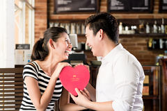 Azjatycka para ma datę w sklep z kawą z czerwonym sercem Zdjęcia Stock
