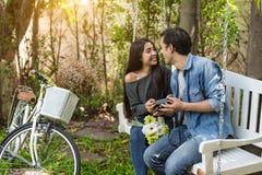Azjatycka para ma kontakt wzrokowego jako romantyczny moment przy ławką w n fotografia stock