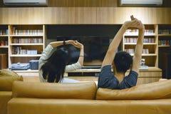 Azjatycka para rozciąga out ich ręki przed TV przy nocą fotografia stock