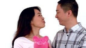 Azjatycka para trzyma prosiątko banka podczas gdy całujący ilustracji