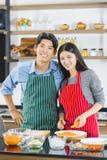 Azjatycka para w fartuch pozach kamera w kuchni zdjęcia stock