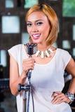 Azjatycka piosenkarza inscenizowania piosenka w studiu nagrań Fotografia Stock