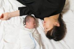 Azjatycka potomstwo matka i jej nowonarodzony dziecko śpi pokojowo na jej łóżku obrazy stock
