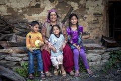 Azjatycka rodzina uśmiechnięta matka i młode dzieci siedzimy na skały ściany outside domu Zdjęcie Stock
