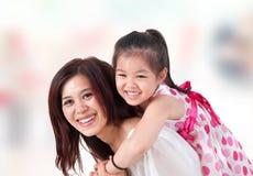 Azjatycka rodziny piggyback przejażdżka w domu. Obraz Stock