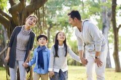 Azjatycka rodzina z dwa dziećmi ma zabawę w parku zdjęcie stock