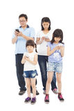 Azjatycka Rodzinna pozycja i używać mądrze telefon wpólnie Fotografia Royalty Free